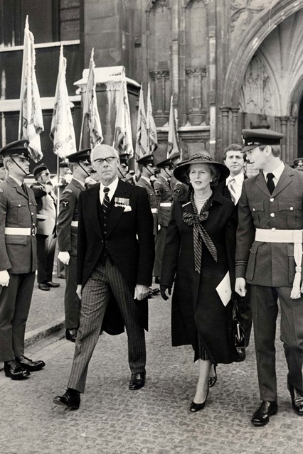 1979  At Westminister Abbey with husband Denis wearing a signature pussy bow blouse.