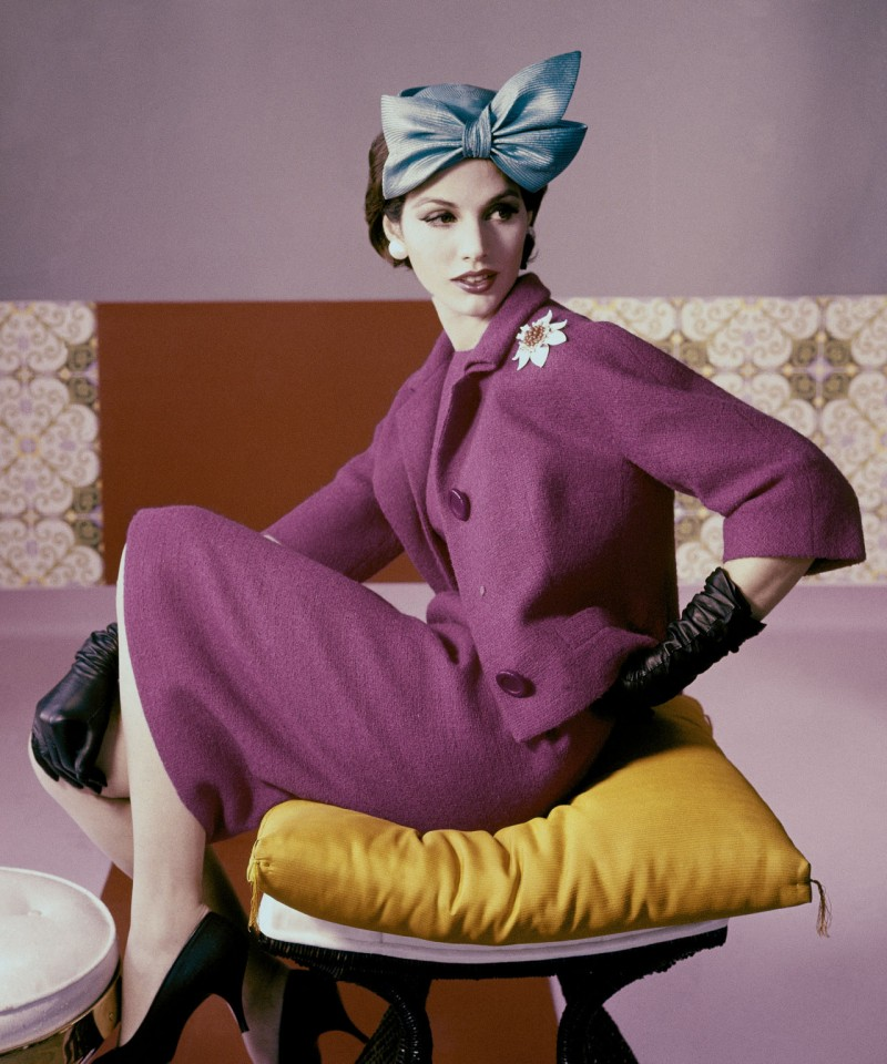 A model wears a fuchsia dress suit and hat with bow detail by Emme, 1961