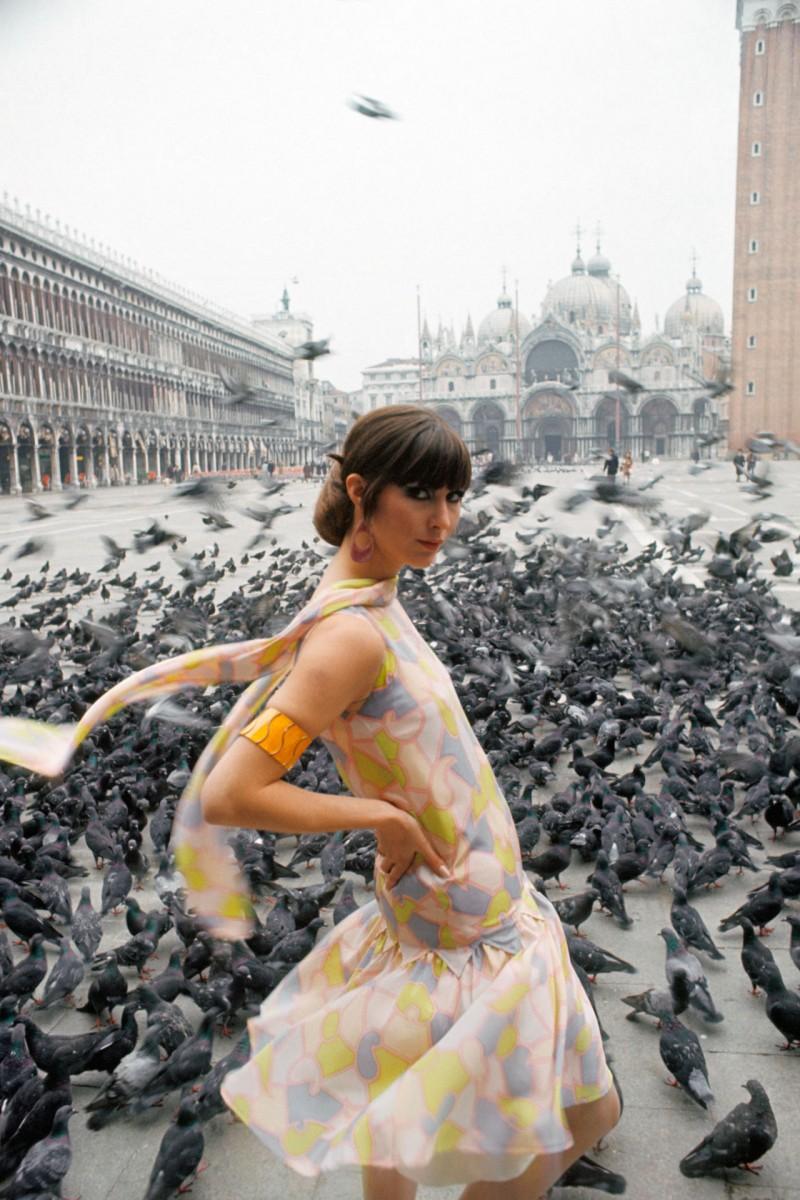 A model wears a multi-coloured silk summer dress in the Piazza San Marco, 1966.