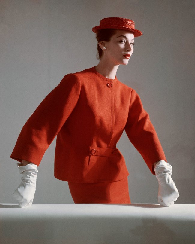 A model wears a red linen suit by Balenciaga, 1952.