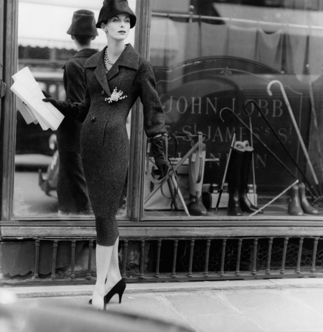 A model wears a tweed coat dress and hat by Dior in London, 1955.