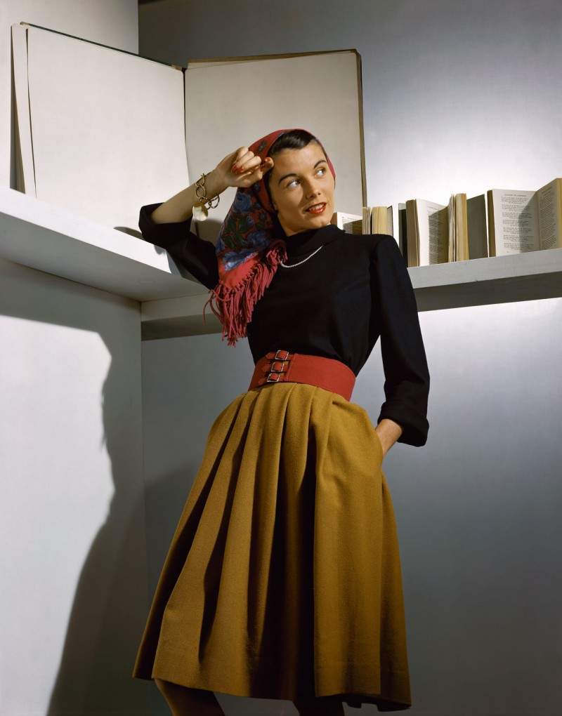 A Vogue model photographed in a camel-coloured wool skirt accessorised with a wide red belt, a fringed scarf and pearls, 1941.