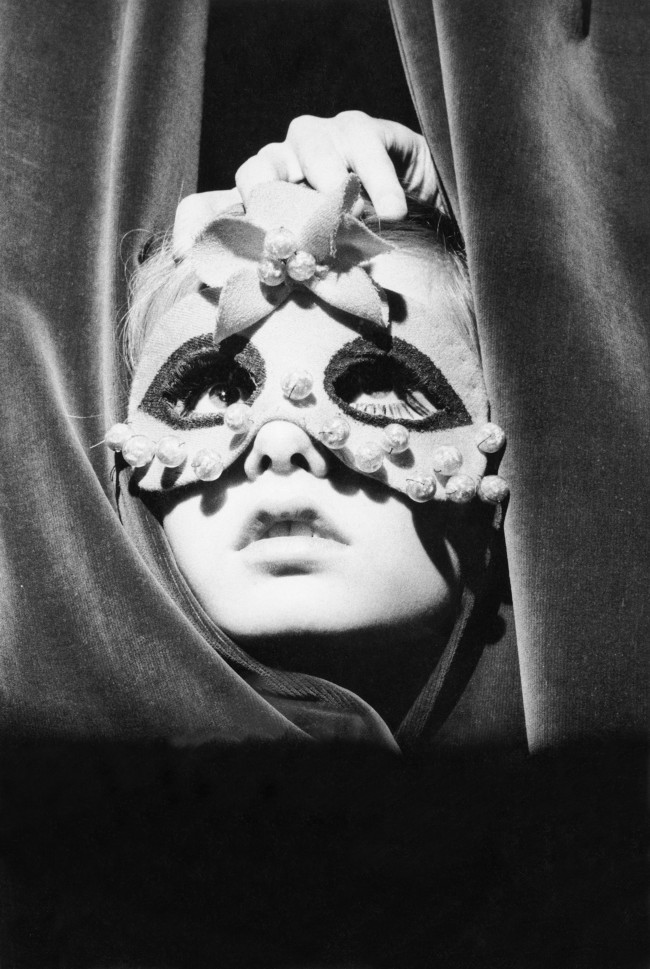 A young Twiggy wearing a mask and peeking through the curtains of the Paris shop Torrente, 1967.