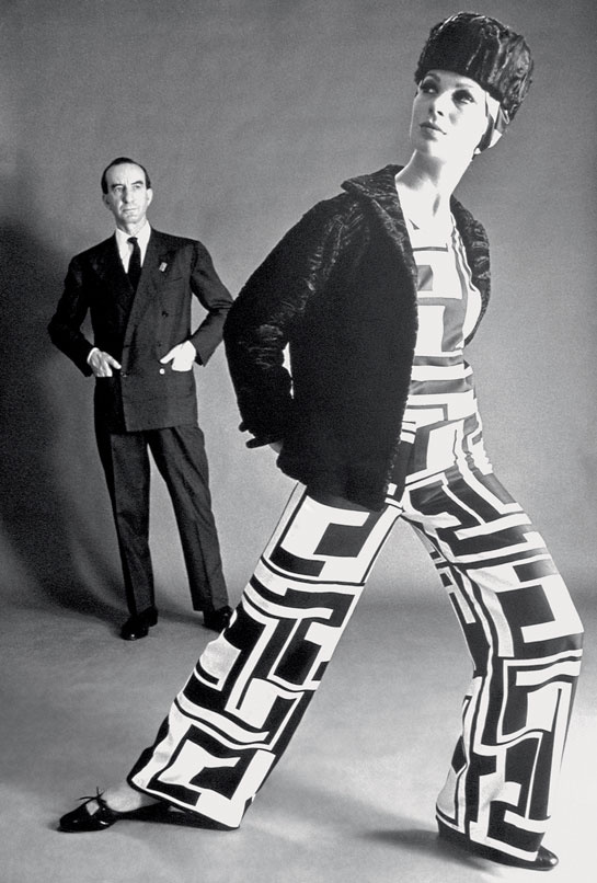 Marquis Emilio Pucci and model wearing Palazzo pyjamas in printed silk in the Torre motif, with jacket and hat. Fall/Winter 1966 Collection. © Serge Libis, Emilio Pucci Archive, Florence