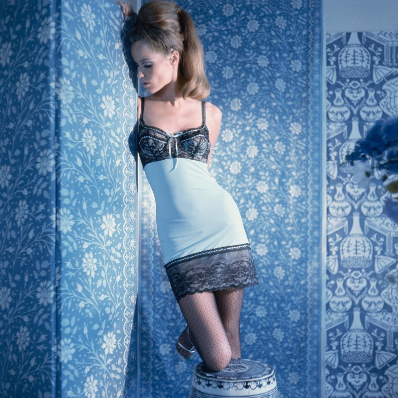 Legendary Vogue model Veruschka in a ribboned chemise by Van Raaltem posed against wallpaper by Clarence House. Photographed in 1965 by Horst P. Horst