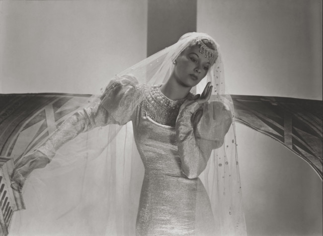 Lisa Fonssagrives models a wedding dress with a pearl-decorated yoke and pearl-studded veil, 1938.