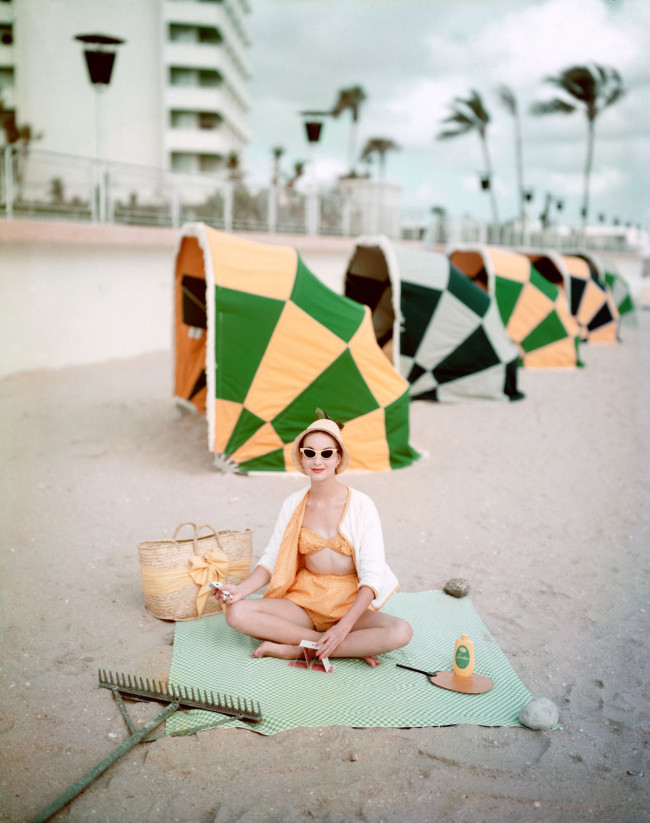 Model on beach in front of Diplomat Hotel, Florida, in calico print swimsuit and terrycloth cardigan, 1959.