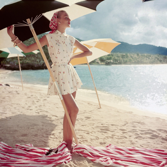Model standing under beach umbrella wearing a summer dress, 1954.