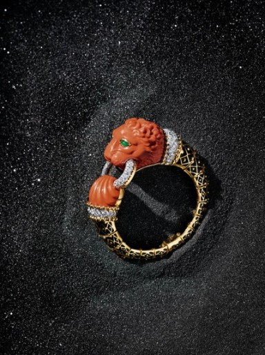 David Webb Carved coral lion cuff with diamonds, black enamel and emeralds. USA. $135,000